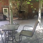 Rocking chairs around the outdoor fireplace under the grape arbor.