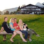 Gastgeberfamilie mit Hotel im Hintergrund