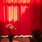 room 103 with the red drapes closed in the sun