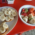 Fresh bagel with peanut butter and banana / fresh fruit bowl.