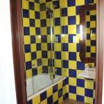 Ruime badkamer met bad/douche.