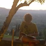 Our son catching the last few rays of daylight reading on the wall in the garden before dinner.