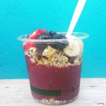 Acai bowl with blueberries, strawberries, blackberries, bananas, granola, honey, chocolate chips