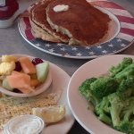 Lemon pepper broiled fish with fruit and broccoli (with an additional plate of pancakes at the t
