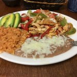 A generous portion of chicken fajitas with refried beans, rice and corn tortillas.