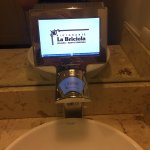 Electronic ads on sink faucet in restroom.