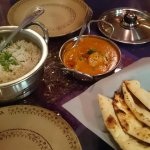 Delicious butter chicken, rice and naan bread.
