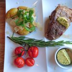 Grilled sirloin steak, grilled cherry tomatoes, rucola parmesan potatoes and Café de Paris butte