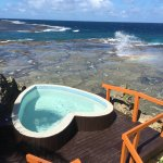 Romantic heart-shaped hot tub overlooking an ocean blow hole