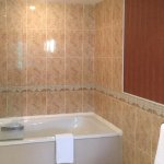One end of bathroom, quite large room, showing the beautiful shower/tub.