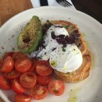 Poached eggs on sourdough toast with avocado and cherry tomatoes