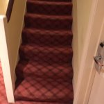 Lethal staircase sowing worn and puckered carpet ending outside a room