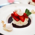 Meringue with strawberries, forest berries sauce
