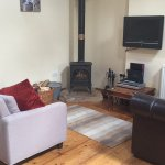 Guillemot Cottage lounge area with Tv and log burner.