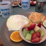 two egg breakfast with biscuit and fruit
