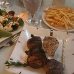 3 filet mignons wrapped in bacon with sauteed mushrooms on the side. Side salad and french fries