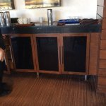 Public view of water station in restaurant with drip stains/filth on cabinetry, garbage and cobw