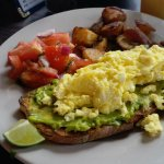 Scrambled eggs and smashed avocado on toast - with tomatoes and roasted potatoes