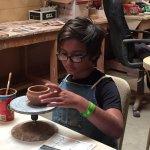 Henri decorating a pot in Rapid City