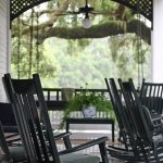 Veranda on front of inn with rocking chairs and porch swing.