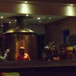 ビールのサー便具をする人バックに醸造タンクその奥に発酵用のタンクがあると思われます。