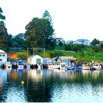 Boat sheds and cafes on the foreshore of Wagonga Inlet in Narooma