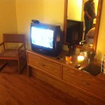 antique television and older furniture and stained lamp shade in newly renovated room