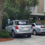 The staff member's car is on the right, in the diagonal lines of the handicapped space.
