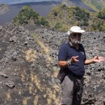 Eddy explaining about the lava flow, with Mount Etna and the broom in the background