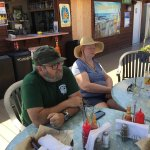Steve and Pam sit under an awning while awaiting their fish and chips and salad respectively.