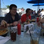 Bonnie, Tricia, and Terri sit under an awning while enjoying a cheeseburger, salad, and sandwich