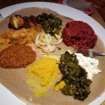 Vegetarian sampler (egg, cabbage, lentils, collards) and kitfo (upper right)