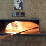 Their secret flavour: Pizza is raised with the paddle to catch the smoke for a few seconds