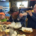 Duluth MN, JUN 2016, a father and sons enjoy chicken at B-Dubs.