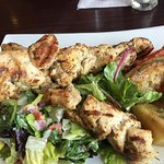 Grilled Marinated Chicken Skewers with Lemon, Lettuce, Tomato, Onion served with Greek Potatoes