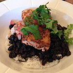 Blacked Mahi Mahi served with black beans and rice, topped with chimichurri and cilantro.