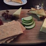 Cheese plate with apple, crackers, bread, dried sultanas