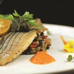 Fillet of Sea bass with a Curcuma Sauce, served with a Creamy Risotto and a Tartar of Olives