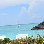 Beach chairs in the foreground, one of the Hobie catamarans you can book (lessons or rides).