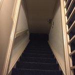 Escaleras para subir a la habitación, abajo está la puerta de la entrada del cuarto.