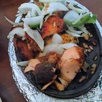 The Tandoori Mixed Grill with chicken, shrimp, salmon, sausage, and goat or lamb