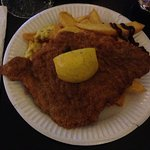 A big piece of schnitzel, on a bed of french fries (chips)