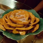 This is the mango flower-shaped dessert. It has coconut cream, mango slices, and sweet rice.
