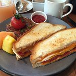 Broken Yolk Sandwich on sourdough bread with aged cheddar cheese & tomato, hash browns on the si