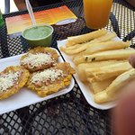 Tostones topped with cheese; Yuca fries with Cilantro sauce