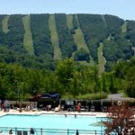 View from indoor pool area looking down at the outdoor pool and Jiminy Peak in the distance