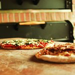 Pizza baked in our wood-fire brick-oven.