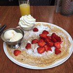 Pancake with fresh strawberries, ice cream, and whipped cream!