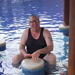 My husband pretending to play the bongos on a seat in the pool... funny guy