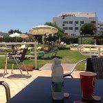 en la terraza del bar al lado de la piscina y en frente del area recreativa